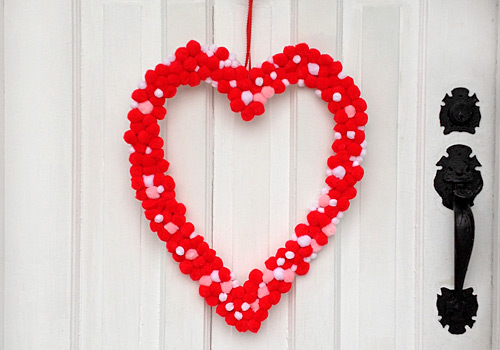 Do you love homemade Valentine's Day kids crafts? We sure do! This brightly colored Pom Pom Heart Wreath is full of whimsy and sensory fun!