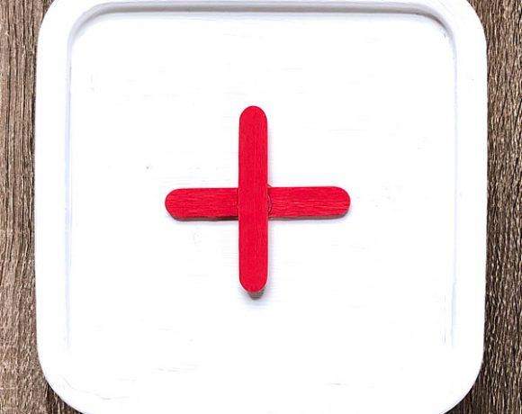 plastic box painted white with red popsicle stick cross
