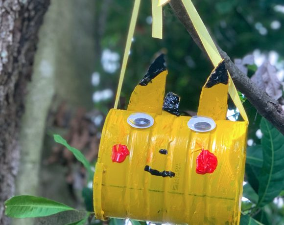 Pikachu coffee can hanging from tree branch with bird seed