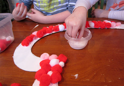 Do you love homemade Valentine's Day kids crafts? We sure do! This brightly colored Pom Pom Wreath is full of whimsy and sensory fun!